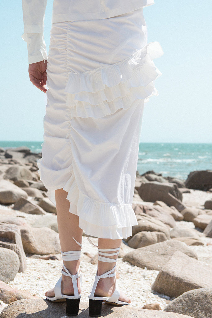 The Aurélie Skirt in White featuring layered ruffles and cut on a bias. Asymmetrical hem. Concelaed side zip closure. Layered ruffles. Partial lined. High rise.