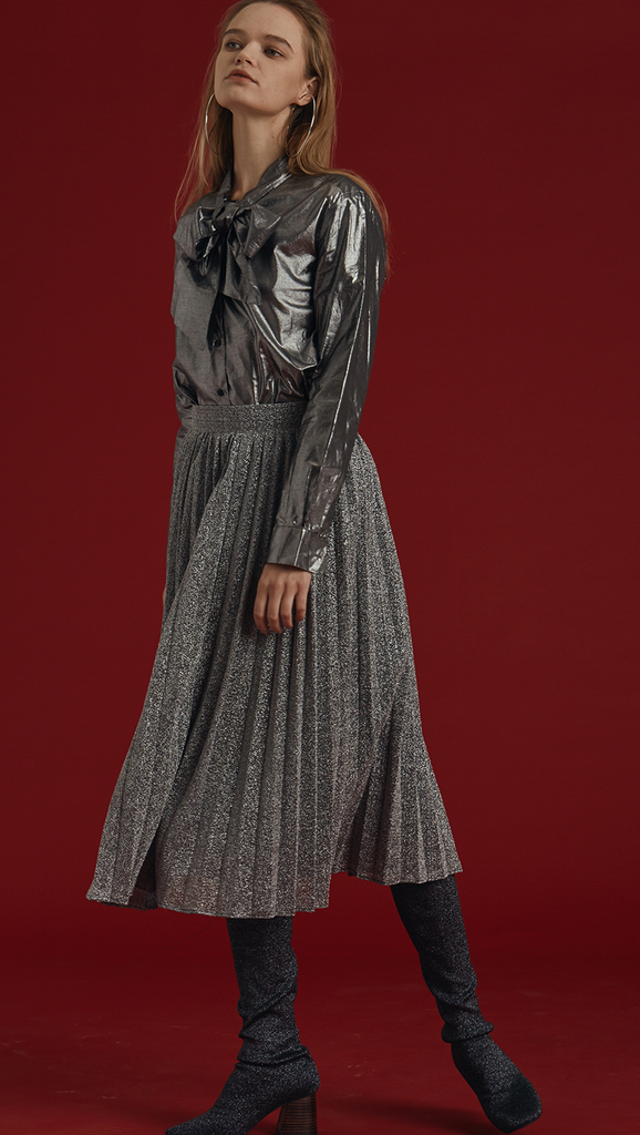 The Blaine is a button-down blouse in glitter sliver metallic. With a self-tied bow, long sleeves. Coated foil.