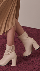 Ayala Midi Boots in Cream Ivory. Soft synthetic leather upper, slouchy design in almond toe and zip opening at back with snap buttons.