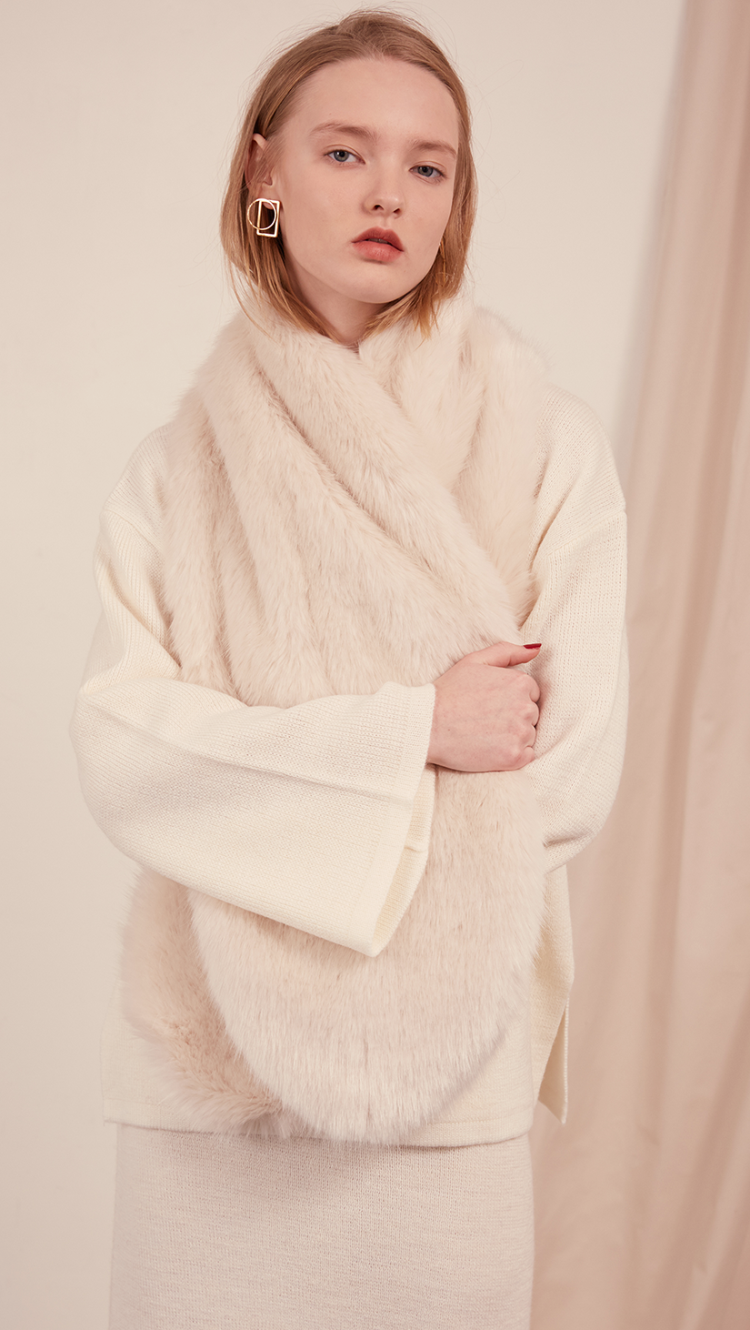 The Beaumont Scarf in faux fur. It features a cream ivory with a neat slip-through fastening and also can be layer it over the lapels of outerwear.