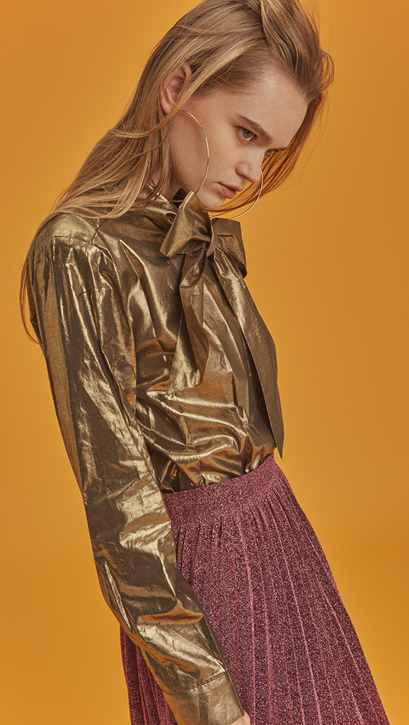 he Blaine is a button-down blouse in glitter gold metallic. With a self-tied bow, long sleeves. Coated foil.