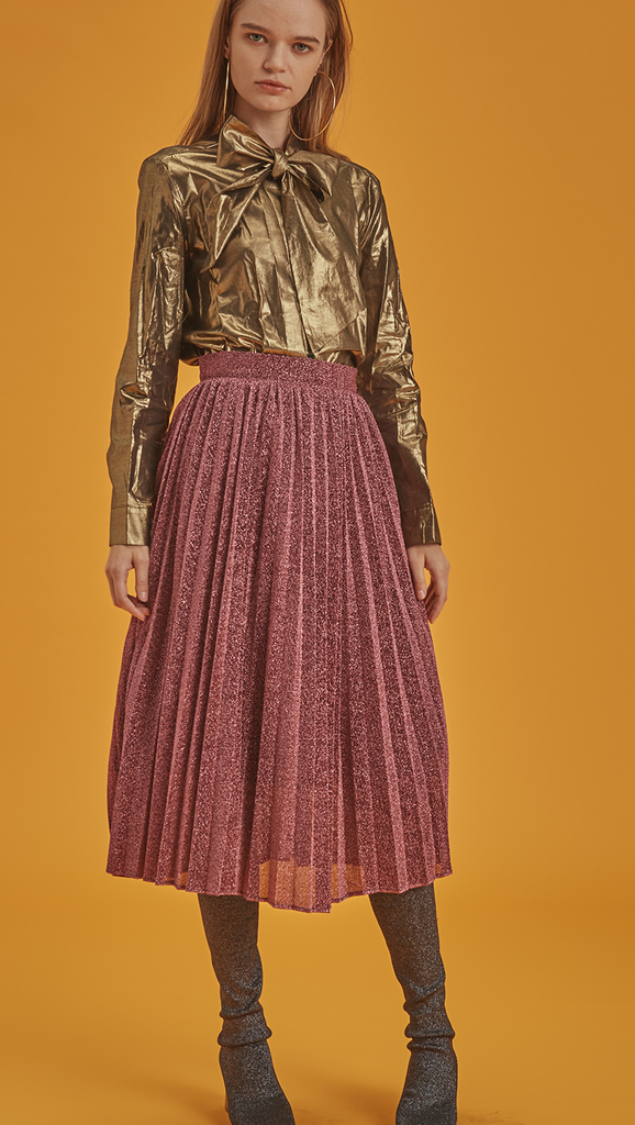 The Blaine is a button-down blouse in glitter gold metallic. With a self-tied bow, long sleeves. Coated foil.