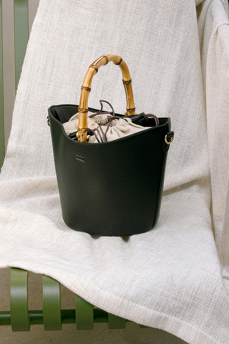 Bonet bag in Black. Wooden bamboo carrying top handles. Cylindrical design. Brown drawstring fabric insert with white tassel.