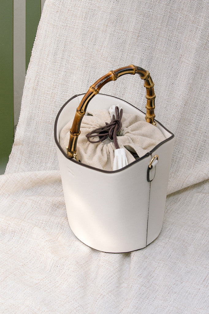 Bonet bag in White. Wooden bamboo carrying top handles. Cylindrical design. Brown drawstring fabric insert with white tassel.