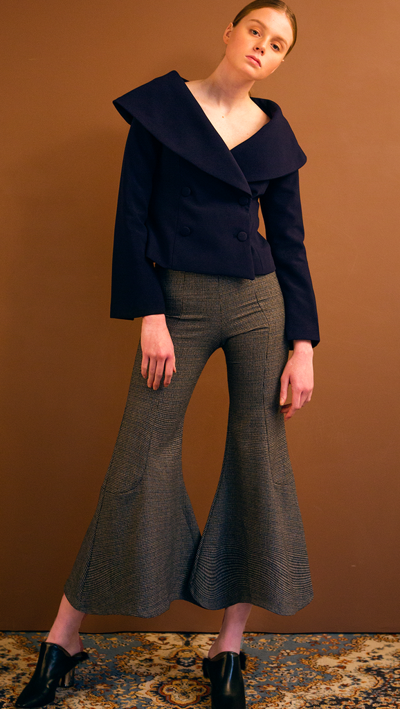 The Helena Pant is black houndstooth wide trouser sit high on the waist with an flared hem. Concealed zip closure along side. Wide leg cut. No pocket. Slim fit. Particularly wide hem.