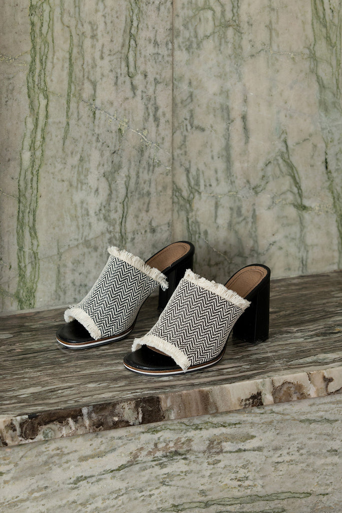 The Brioni sandal in Black-and-White chevron pattern. Open toe. Wool carpet fiber upper with tassel detailing. Slip-on design.