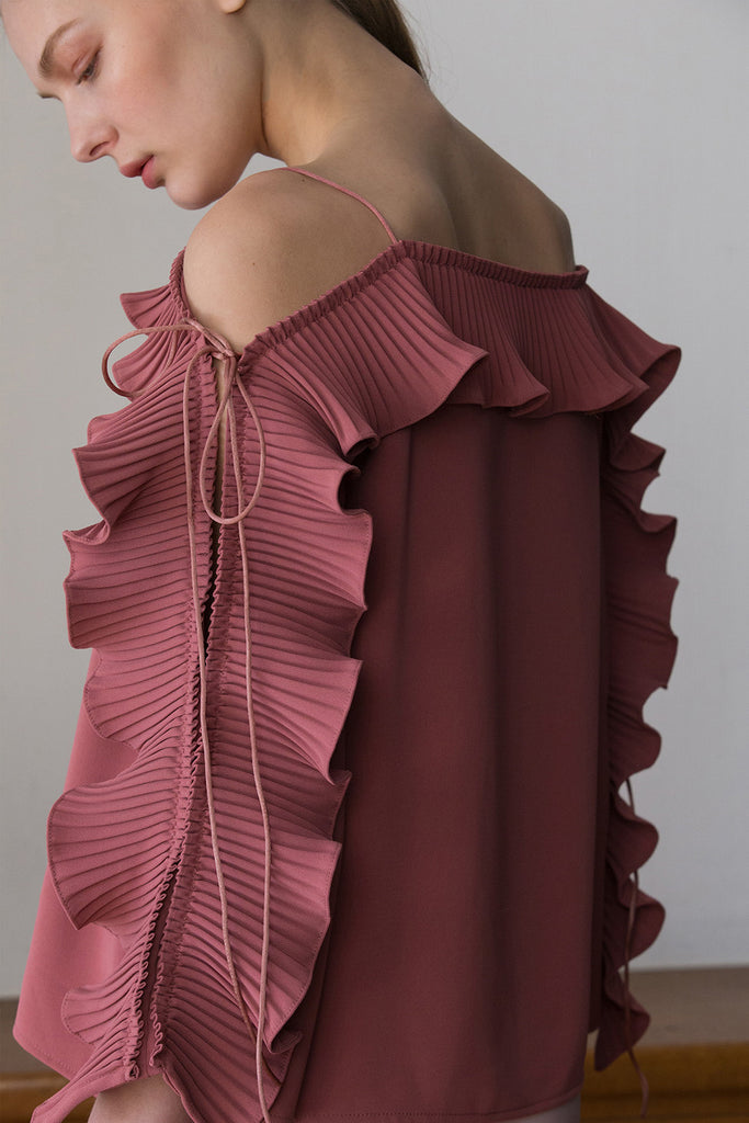 The Calin Top in Pink, featuring thin straps, square neckline, dimple sleeves in ruffle detailing with self-tie. Pull on.