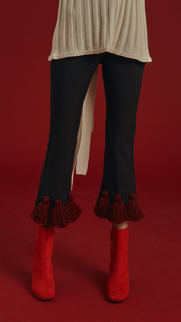 The Capoté Pant is mid-waisted, cropped black trousers with red tassles detailing in Burgundy. With button and zip closure at front, two pockets, ankle length.