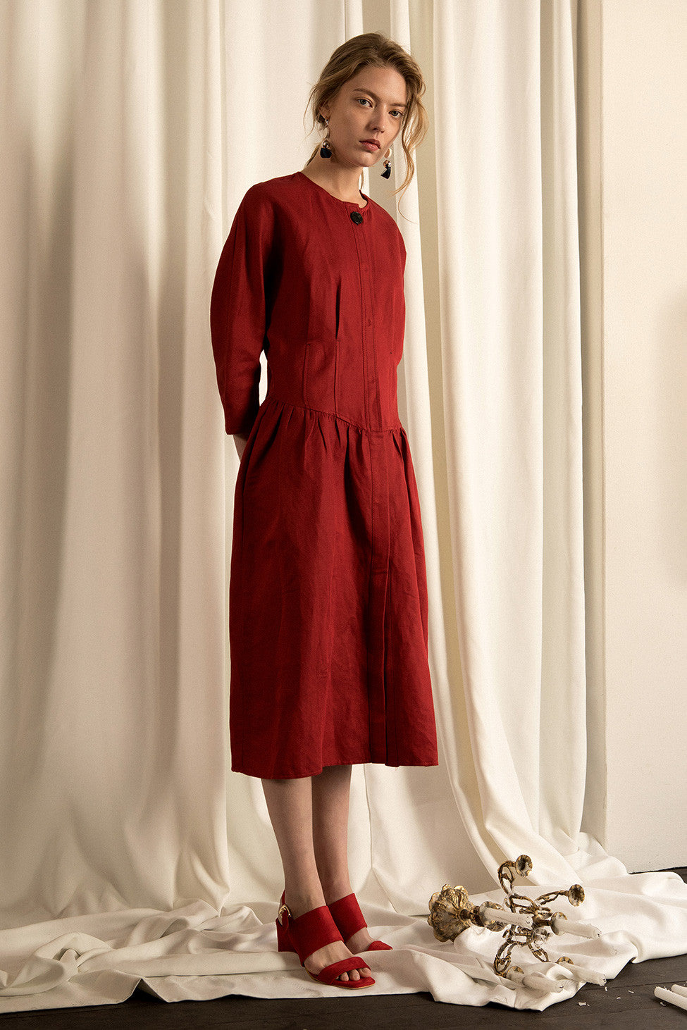 The Carmen Dress in Oxblood, featuring round neckline, concealed full button placket, straight yoke with exaggerated center pleat.