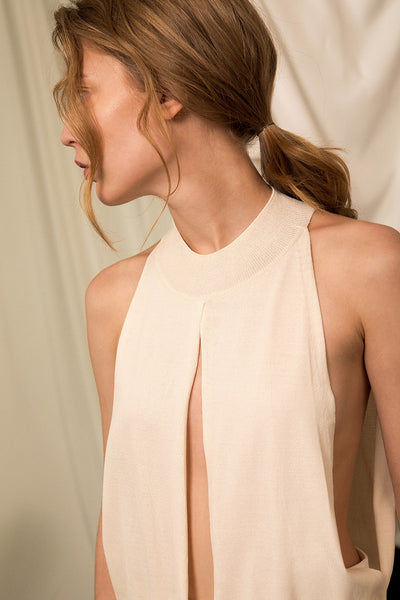 The Cecchetti Knit in Ivory, featuring mock neckline, deep slits at torso with cutout detail underneath. High-low hem. Straight silhouette. Please note that this is a fragile fabric. No returns will be accepted.