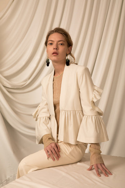 The Cecil Jacket in Ivory, featuring collarless, bracelet sleeves, exaggerated box pleat and open back with ruffle details at elbow. Lightweight.