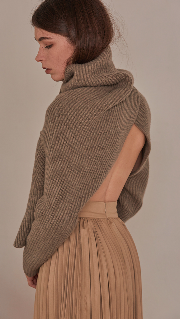 Cecil Sweater, a knit sweater in beige. Rollback collar with pointed wide cowl neck. Drop shoulder design, open rib details. Short length in open back. Designed to be loose fit.