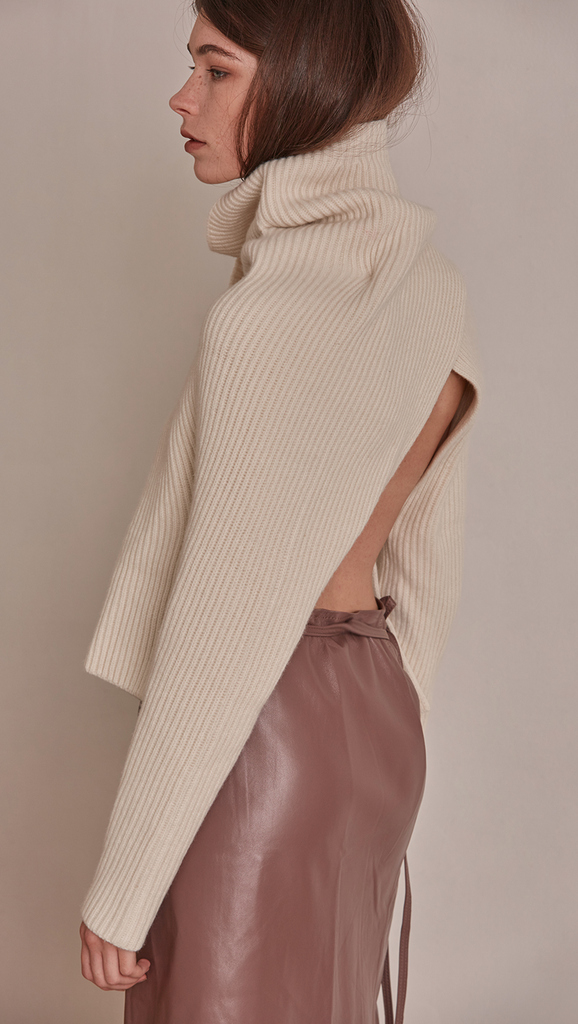 Cecil Sweater, a knit sweater in cream ivory. Rollback collar with pointed wide cowl neck. Drop shoulder design, open rib details. Short length in open back.