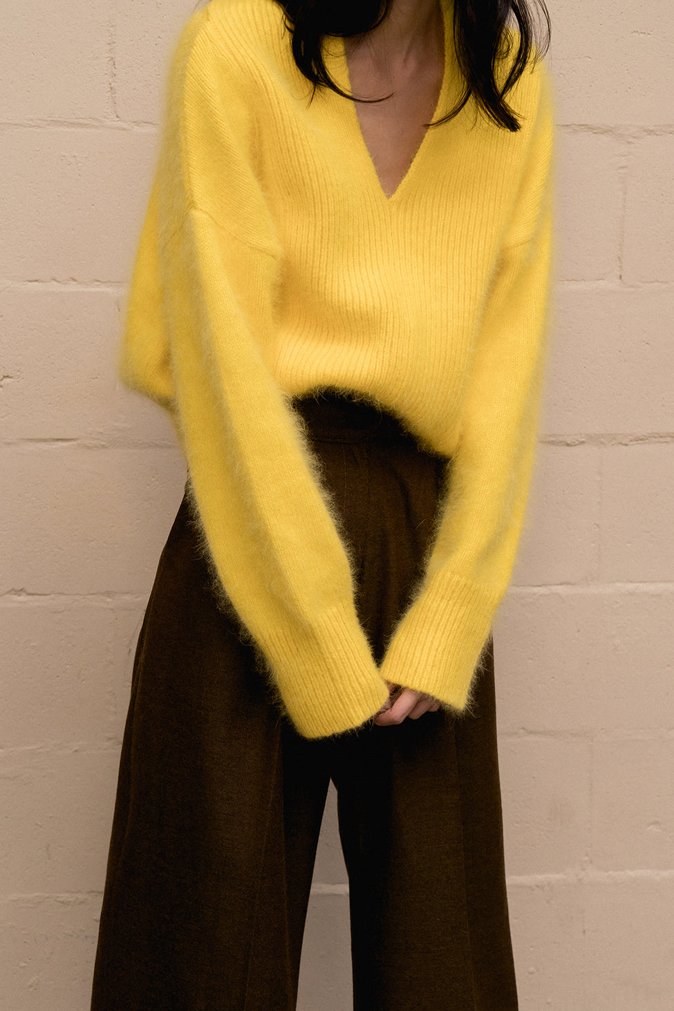 The Cecily angora sweater, long sleeved pullover with deep V-neck in yellow lambs wool blend. Dropped shoulder.