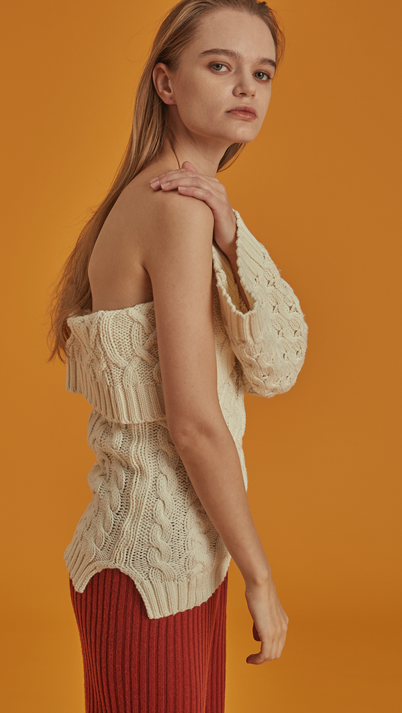 Celina is a cable knit in Ivory with a flattering one-shoulder silhouette. Drop shoulder design, long sleeve, detachable shoulder strap in button closure. Pull on. Straight fit.