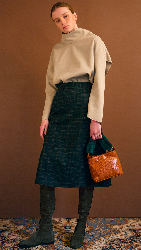 The Charlie Skirt in patterned with green plaid. With a high-waisted polished A-line style with back ruffle details. Over-the-knee length. Concealed zip closure. No pockets.