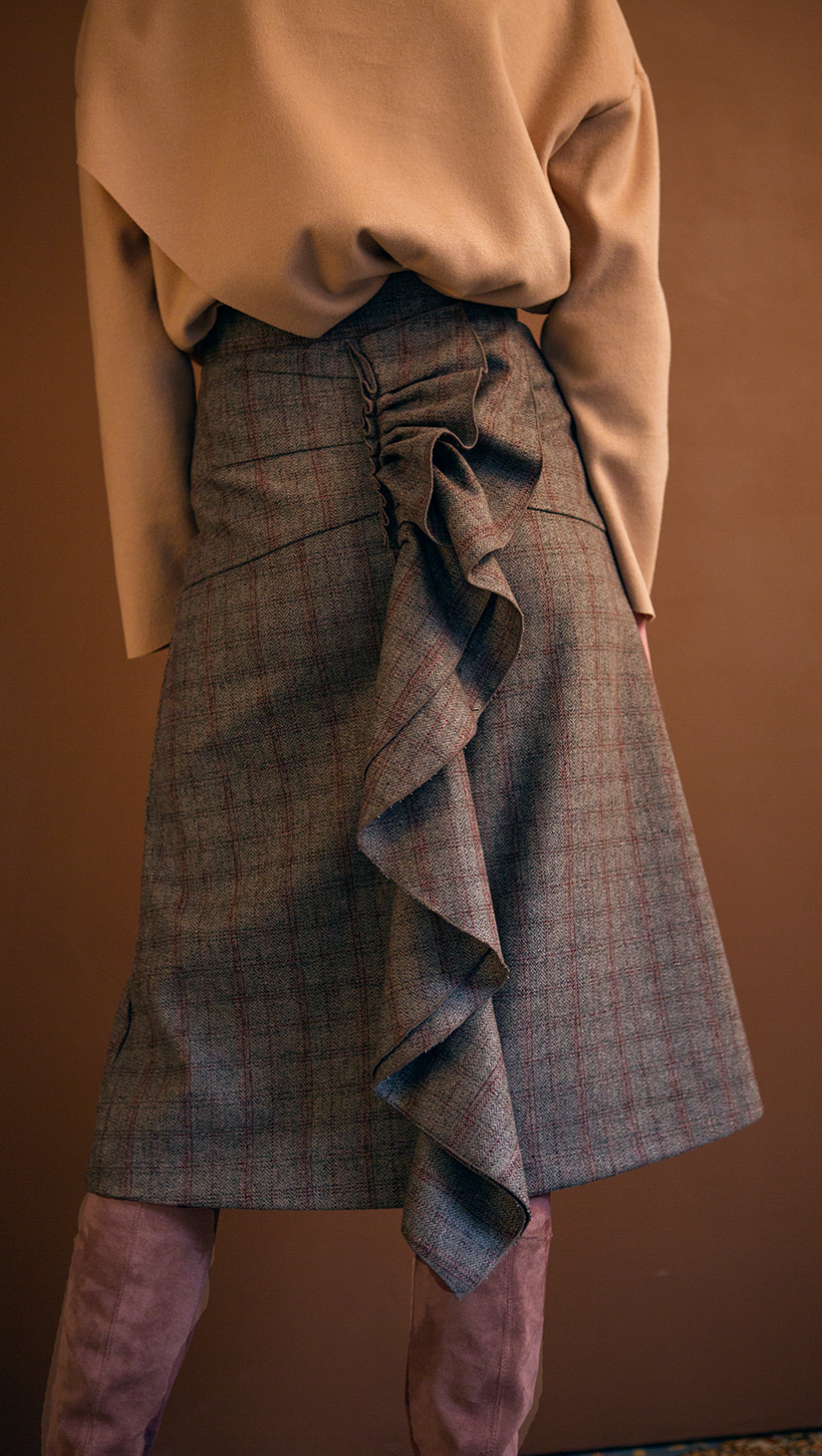 The Charlie Skirt in patterned with grey plaid. With a high-waisted polished A-line style with back ruffle details. Over-the-knee length. Concealed zip closure. No pockets.