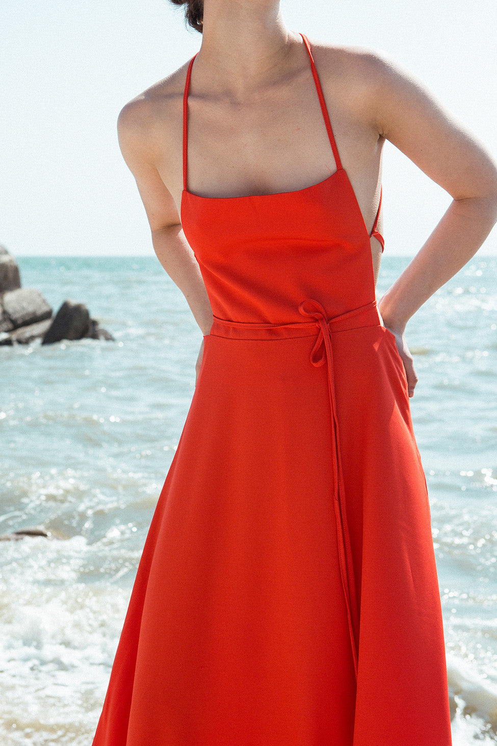 Long slip dress in rose featuring straight square neckline with thin shoulder straps. Darts at bust. Concealed zip fastening at the back. Open back with self tie. Partially lining.