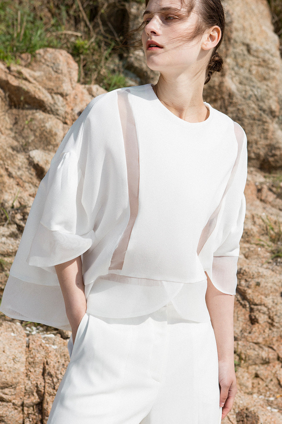 The Cicely Top in White featuring round collar, dropped shoulder, octopus sleeve. Concealed side zip closure at one shoulder. Pull on.