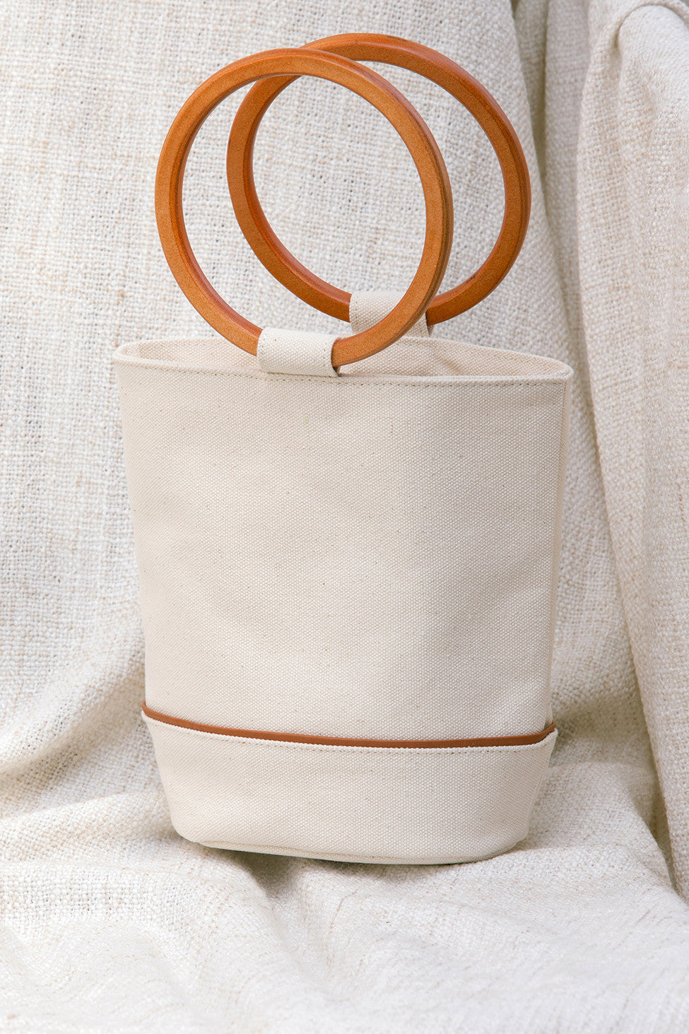 Main compartment with loop closure. Carrying wood handles. Fully lined. Cylindrical design