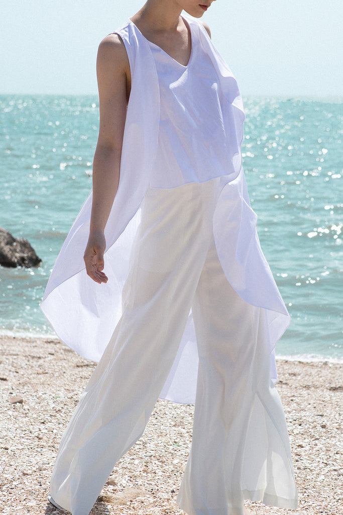 The Cincinnati Top in White featuring v-neckline collar, waterfall ruffles with sleeveless. Pull on.