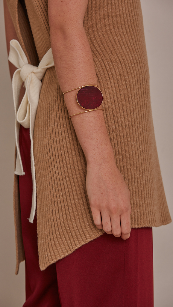 Claudé Bracelet, gold plating cuff with free moving burgundy marble discus circle.