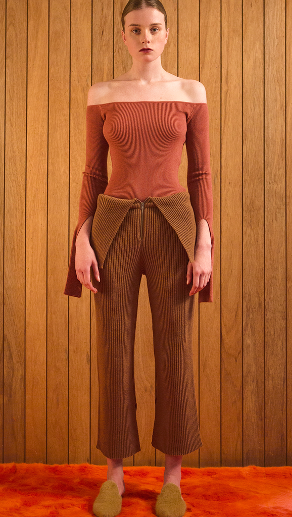 The Ellin OTS Sweater in Dusty Pink. Features off-the-shoulder silhouette with cut out cuffs. Pull on. Slim fit.