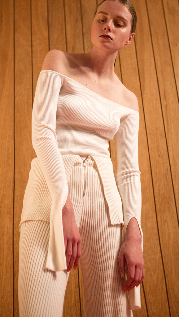 The Ellin OTS Sweater in Ivory. Features off-the-shoulder silhouette with cut out cuffs. Pull on. Slim fit.