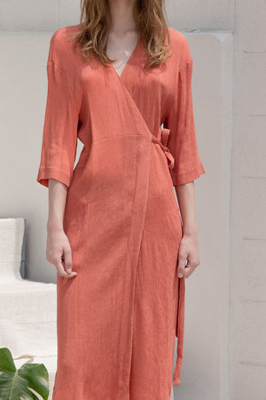 The Corinna pleats dress in wrap front with sash belt, side slits, quarter sleeves. Pull on.