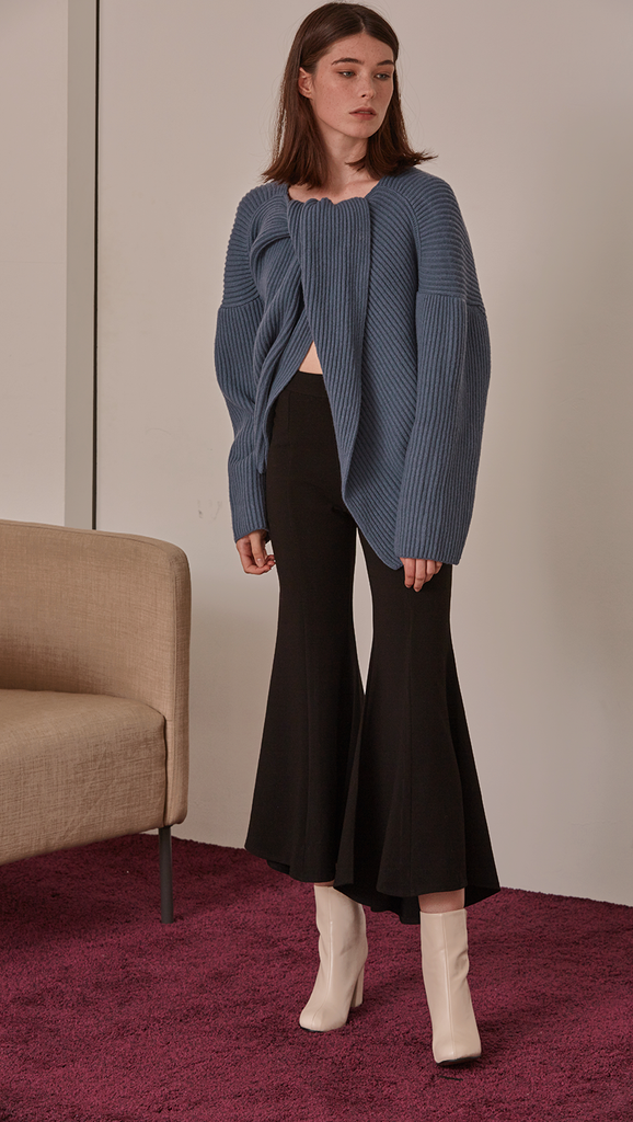 Darah Sweater, a knit sweater in blue. THigh-low length. Twisted opening collar with pointed wide round neckline. Drop shoulder design, open rib details. Short length in open back. Designed to be loose fit.