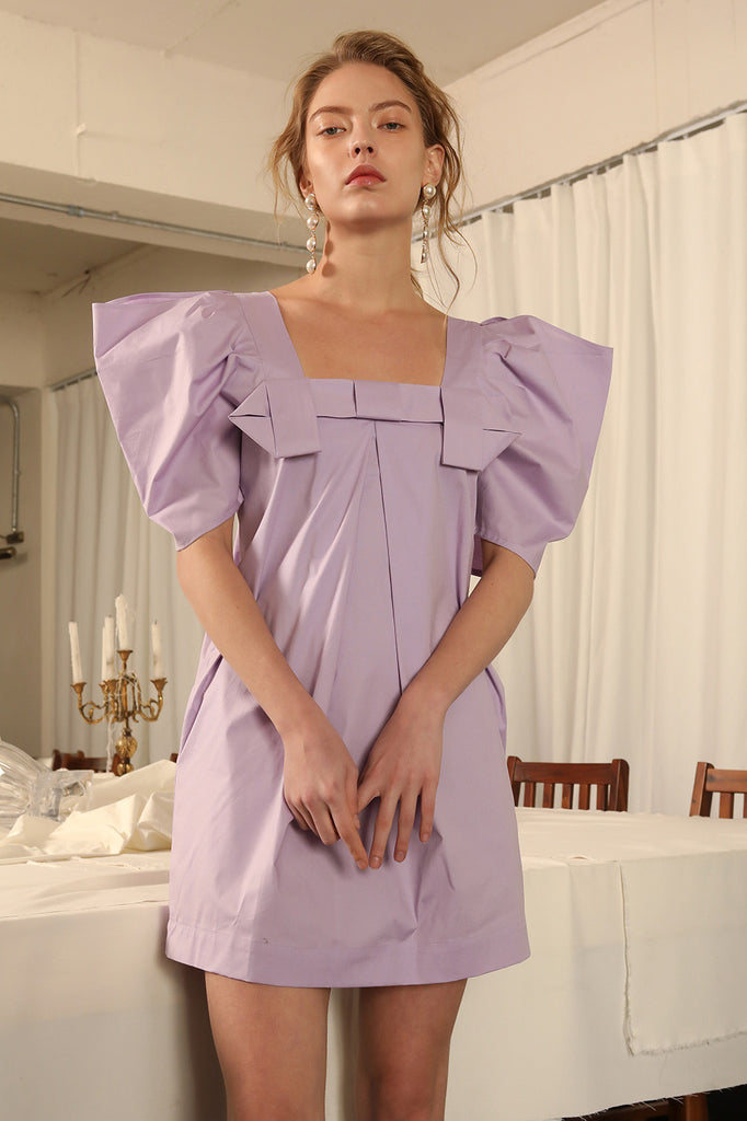 The Deja Dress in Mauve, featuring square neckline with origami detailing, raglan along the sleeves to create a voluminous, puffed effect with upper slits, concealed zip closure at back. Mini skirt length.