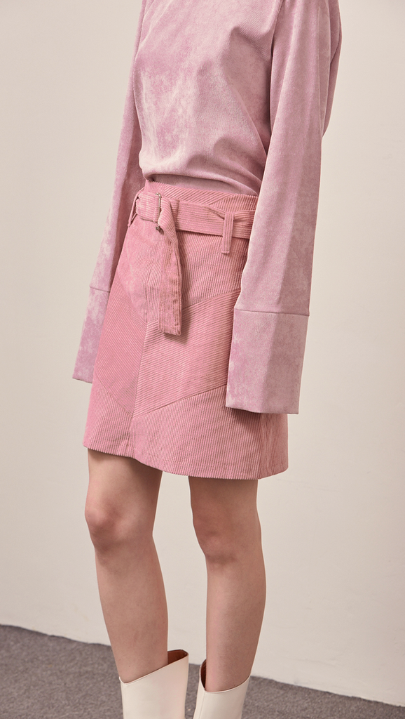 The Ellie Skirt in pink corduroy. With a high-waisted polished A-line style with belt loops. Knee-length skirt.