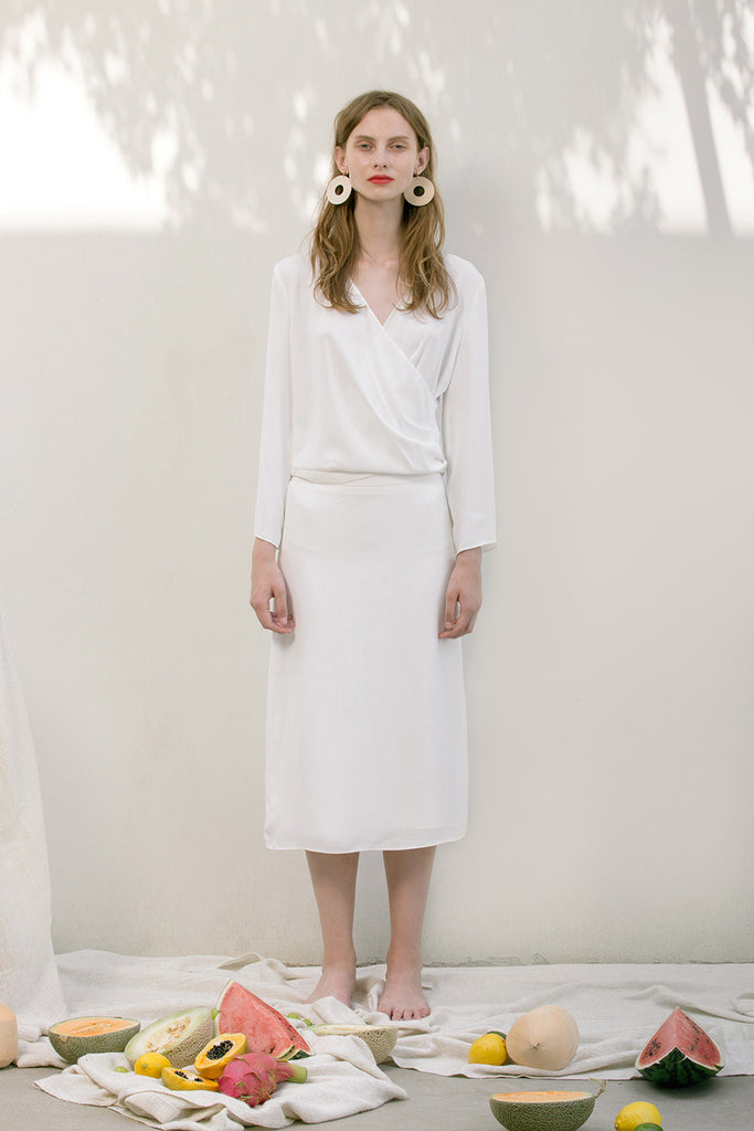 The Emmeline Skirt in White featuring fluted hem and elasticated waistband at back. Side slits. No pockets. Partial lined.