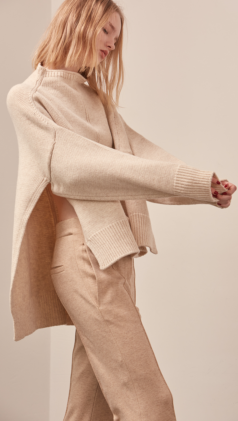 The Erin Sweater in soft oatmeal. Features rolled neckline, long sleeves, drop shoulder, side slits. Pull on. Relaxed silhouette.