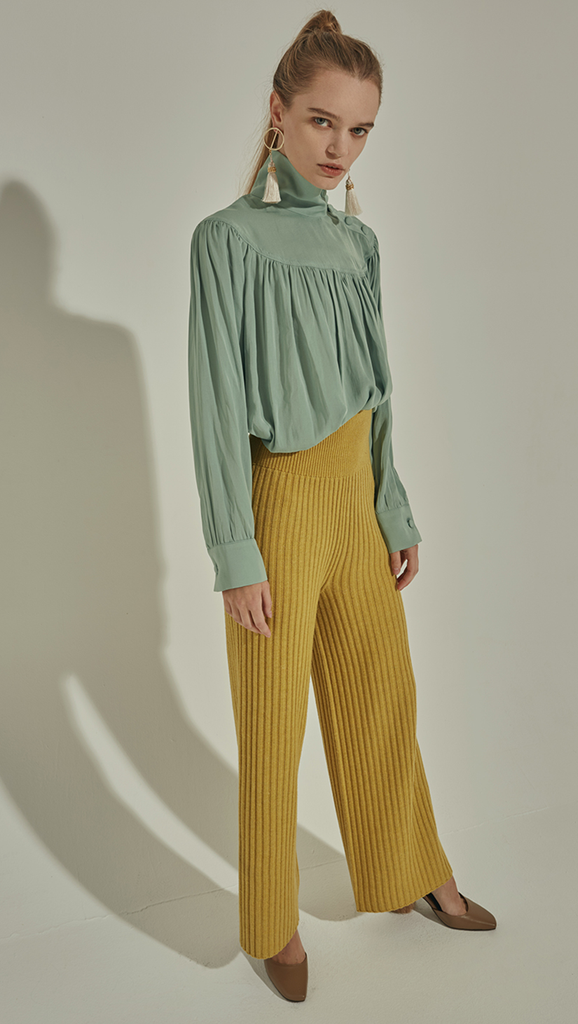 Faé Blouse in Mint. Soft-touch. High turtleneck collar with button closing, button closure at cuff. All-over raglan detailing. Designed to be loose fitting and relaxed.