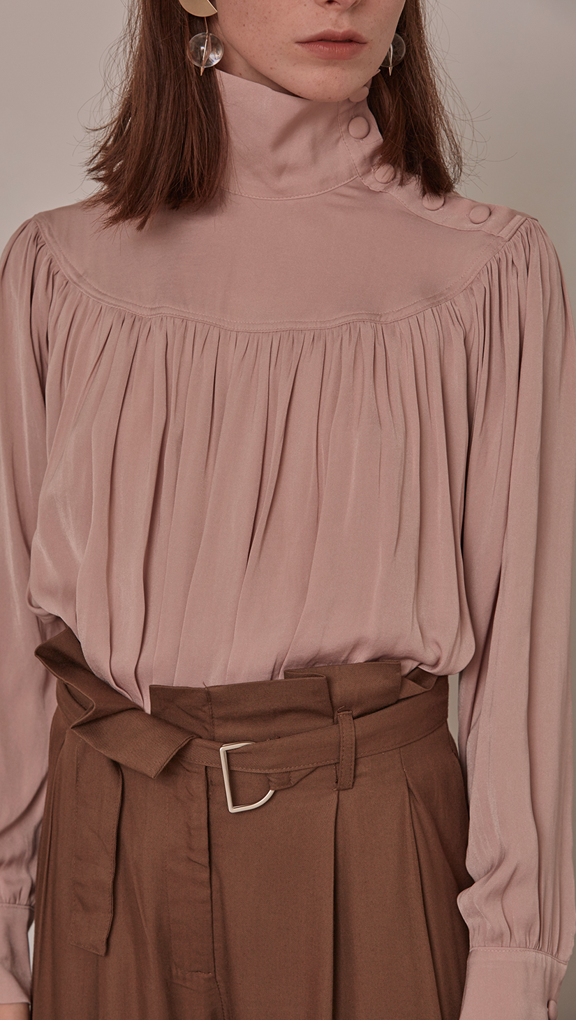 Faé Blouse in Pink. Soft-touch. High turtleneck collar with button closing, button closure at cuff. All-over raglan detailing. Designed to be loose fitting and relaxed.