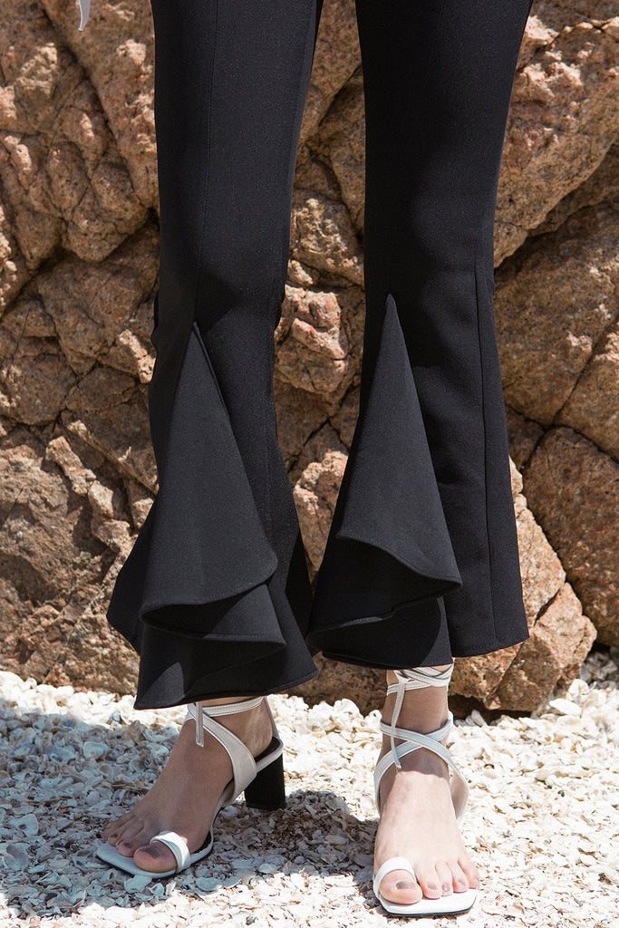 The Faroe Pant in Black featuring mid-rise peplum draped ruffle on leg. Centre concealed zip and hook and bar closure.