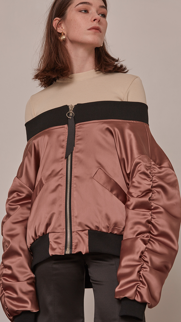 Farrow Off The Shoulder Bomber Jacket in Gold. Lustrous gold satin with oversized long ruched sleeves. Elastic off-the-shoulder banding. Front slit pockets. Zip fastening through front. Fully lined. Mid-weight. Designed to be loose fit.