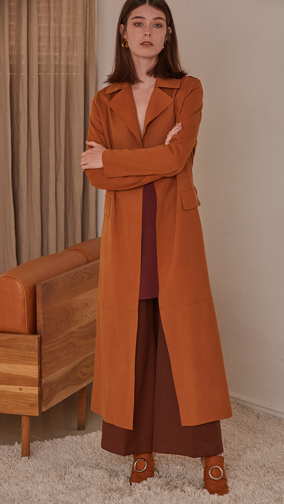 Vegan suede robe coat with tie in camel. No hardware, centre front tie closure. Pointed lapel collar and two oversize slip pockets at natural waist. Super soft suede feel. Straight hem. Designed to skim the body and have a dropped shoulder seam.