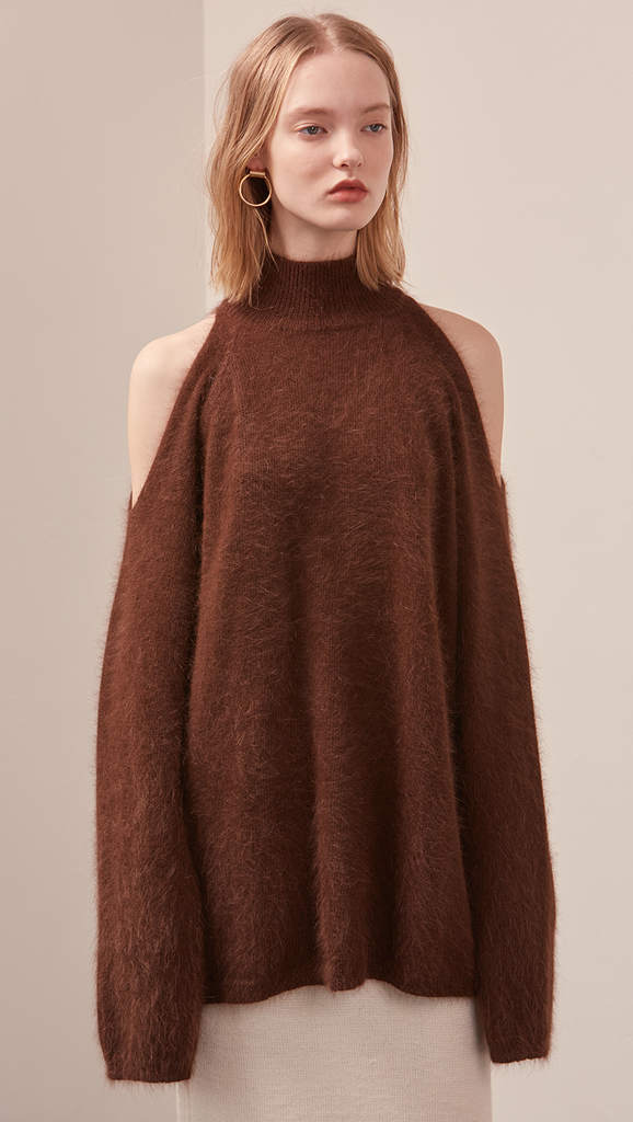 The Fella Sweater in dark brown. Features rolled neckline, long sleeves, drop shoulder, side slits. Pull on. Relaxed silhouette.
