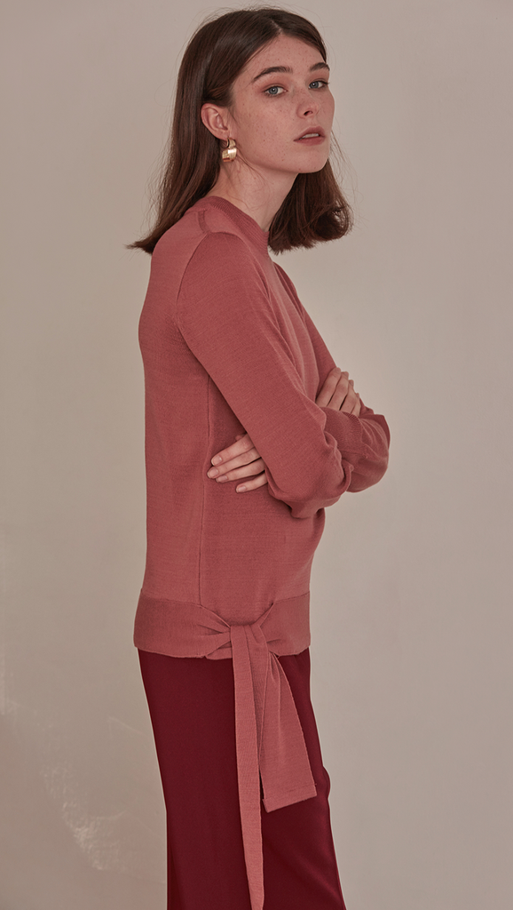 Féte Sweater in Pink. Crewneck long sleeved lightweight knit. Self wrap tie on the side of hem. Slit at cuff. Pull on. Slim fitting body with a long tie sash.