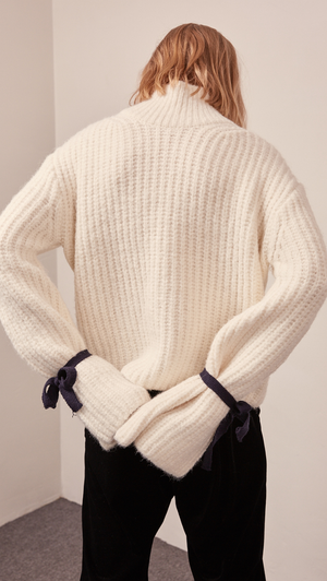 The Finn turtleneck sweater in off-white. Features long sleeve, wide bell cuffs with self-tie straps. Pull on. Relaxed fit.