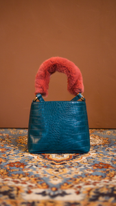Forziéri bag in blue/pink. Fur handle, front flap magnetic snap tab closure. Interior pockets. Detachable shoulder straps. Structured bottom.