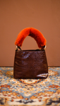 Forziéri bag in tan/orange. Fur handle, front flap magnetic snap tab closure. Interior pockets. Detachable shoulder straps. Structured bottom.
