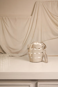 Galante bag in Ivory. Top carry handle, die cut detailing. Inset white canvas throat with drawcord closure. Main compartment with cinch closure and tassel detailing. Detachable shoulder straps.