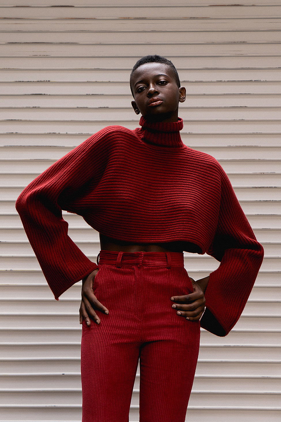 The Gianni sweater in burgundy featuring bell sleeves and cropped hemlines. Ribbed knit from soft, thick wool fits neatly on the shoulder and cuffs but is exaggerated through the arms and chest. It hits just above the bust. Pull on. Relaxed silhouette