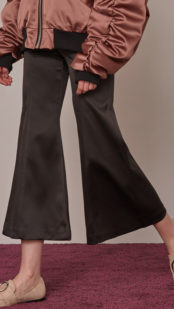 Cropped Gisela pant with flared leg in black. Lustrous black stain feels. Four pocket styling. Zipper fly and tab closure.