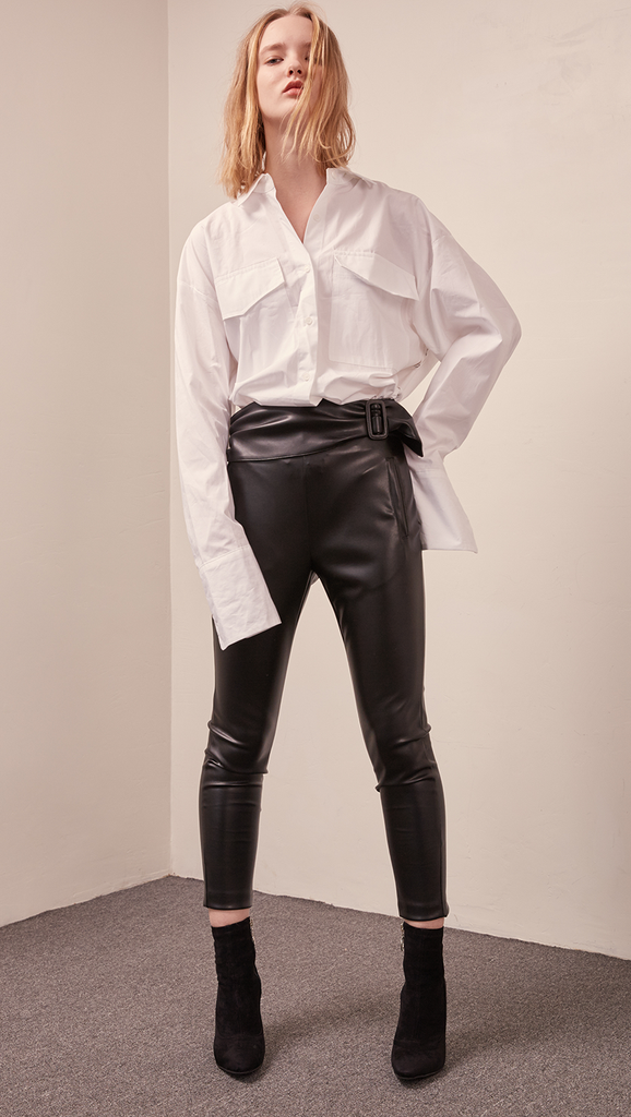 The Gwynn in black stretchy leather legging pant. Streamlining shape that ends above the ankles, buckled straps at the front, slant two pockets, zipper closing. Slim fit. Starchy Fabric.