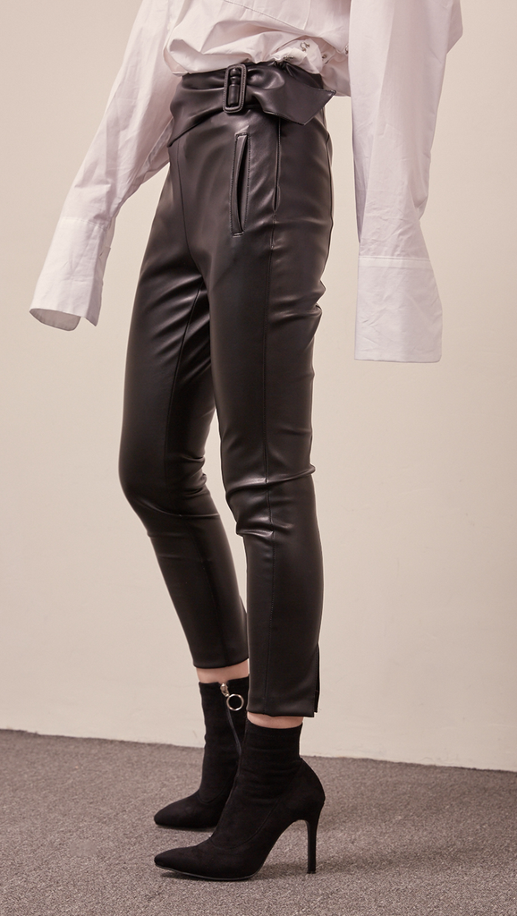 The Gwynn in black stretchy leather pant. Streamlining shape that ends above the ankles, buckled straps at the front, slant two pockets, zipper closing. Slim fit. Starchy Fabric.