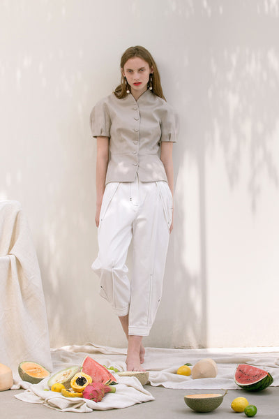 The Hanson Pant in off-white featuring pleats at front waist, slanted front pockets, tapered leg with rolled cuff with button closure. High-waist.
